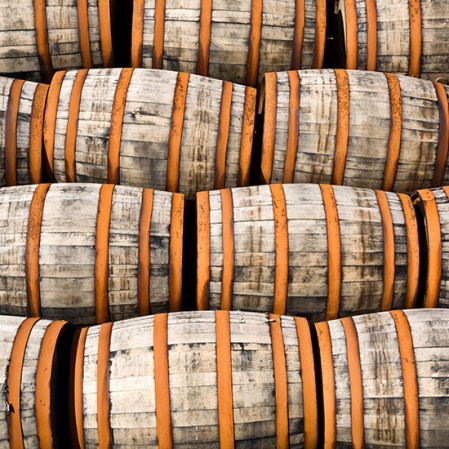 Oak whisky casks stacked in a distillery yard Scotland