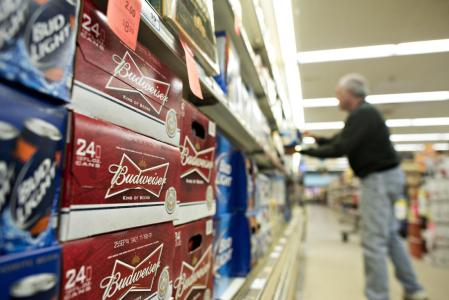A customer shops near a display of Anheuser-Busch Budweiser brand beer in a supermarket in Princeton, Illinois, on October 28, 2014.