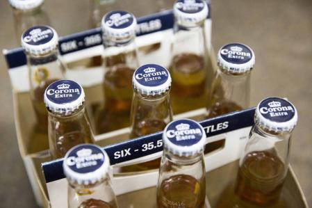 Six packs of bottled Corona beer, produced by Anheuser-Busch InBev NV, sit on display in a store in Paris, France, on Thursday, Oct. 15, 2015. AB Inbev is planning to sell bonds worth as much as $55 billion to finance its $106 billion takeover of SABMiller Plc, setting a record for debt issuance to fund a corporate acquisition, according to people familiar with the matter. Photographer: Christophe Morin/Bloomberg via Getty Images