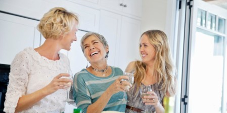 Cheerful two generation women with wine glasses in kitchen