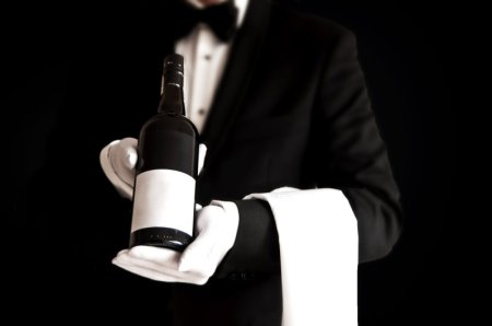 Waiter or sommelier in a tuxedo holding a bottle of wine (Thinkstock)